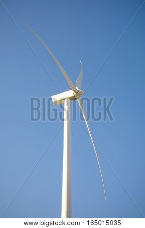 Closeup of windmill turbine and blades generating electricity over a blue sky background. Clean and ecological energy production concept.