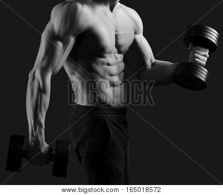 Physical condition on peak. Monochrome cropped shot of a male bodybuilder posing shirtless showing off his sexy abs holding dumbbells