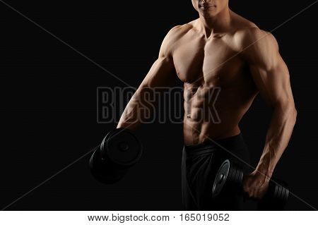 Fitness routine. Cropped horizontal shot of a young fit bodybuilder exercising with dumbbells posing shirtless on black background