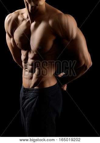 Epic bodywork. Cropped shot of a ripped man body on black background