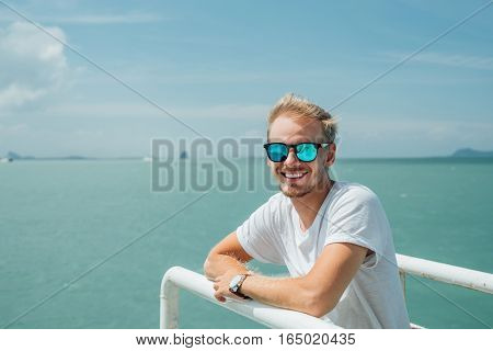 Portrait of a young attractive guy in a white dress and glasses on the background of the celestial landscape. Blonde with glasses in white shirt leaning on the railing of the ship.