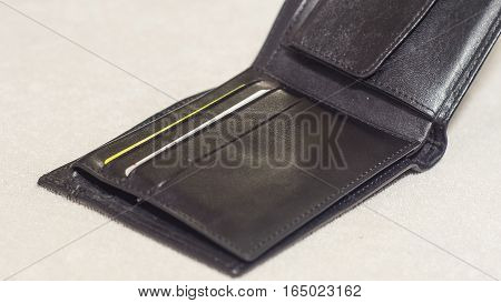 An open black leather wallet on a light background. With credit cards.