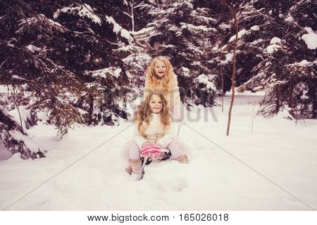 Little girls enjoy a sleigh ride. Children play outdoors in snow. Outdoor fun for family Christmas vacation.