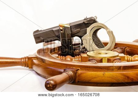 Ships wheel, gun, cuffs and clip with a white background.