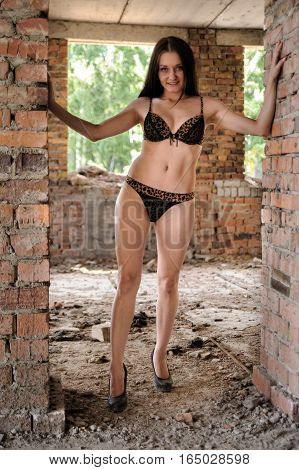 Beautiful sexy woman in lingerie over construction site background.