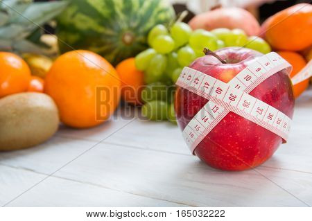 Apple And Measuring Tape Over Fruity Background