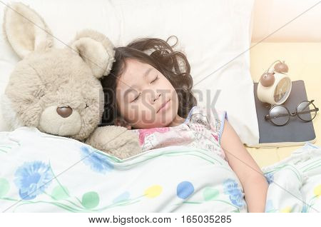 cute girl sleep sweet dream with teddy bear on her bed