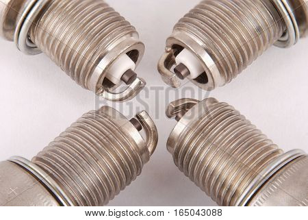 Four new spark plugs on a gray background
