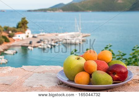 Plate of fruit apple, pear, peach, nectarine, apricot, lemon on the stone terrace overlooking the seascape, sea bay near the peninsula Peloponnese, Greece. Summer fruit plate by the sea. Horizontal.