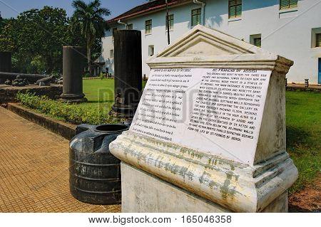 Goa, India - November 13, 2012: Tourist stone sign for tourists in two languages near famous landmark - Roman Catholic Church of St. Francis Assisi, Old Goa, India.