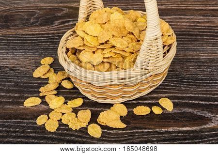 Corn Flakes In Wicker Basket And Scattered Flakes On Table