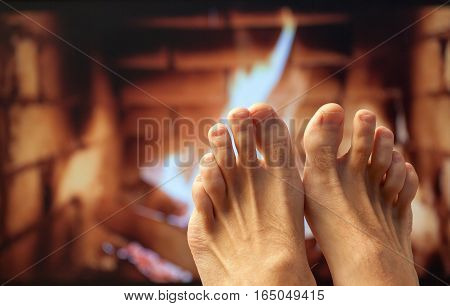 Naked legs are heated by a fireplace.