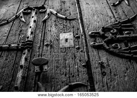 Old wooden textured door with keyhole and metal railings