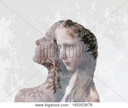 Double exposure portrait of beautiful girl on a background of trees