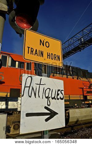 Signs indicates the passing locomotive and train passing through an intersection will not sound off it's horn and antiques available to the right