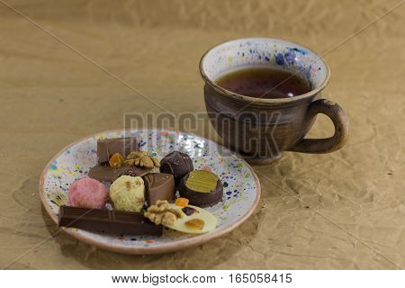 A variety of sweets on the saucer with a cup of tea on background with kraft paper