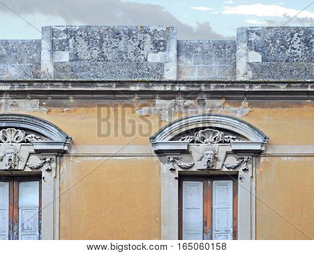 Detail of antique gable with stone faces in Brindisi Italy