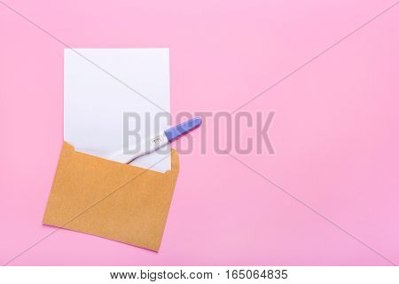 letter with a positive pregnancy test on a pink background