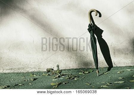 Black Umbrella near gray grunge wall with shadow.Toned image.