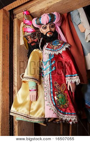 Dolls from a puppet theater weighing on a wall