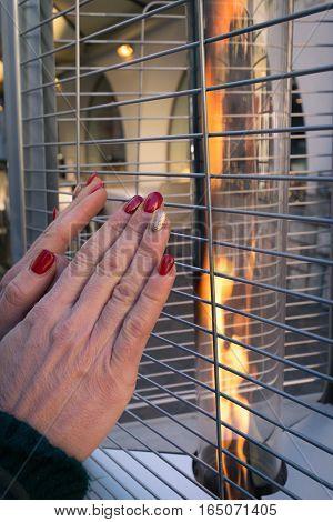Woman warms her hands on a modern street fire.