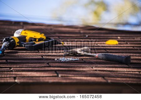 Roof repair. Roofing project on with tool on the roof. Roofing concept. My roof photography. Roof repair on sunny day. Roofer ready to repair roof with nail gun and hammer.