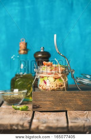 Healthy homemade jar quinoa salad with tomatoes, avocado and fresh basil. Detox, dieting, vegetarian, vegan, clean eating food concept. Bright blue background, selective focus, copy space