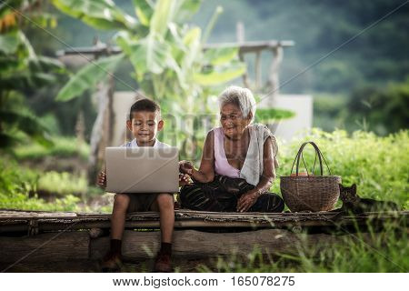 Happy boy and grandmother using laptop Education.