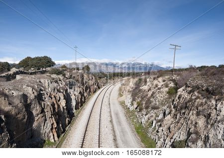 Rail road. At the background, snow capped peaks of the Guadarrama Mountains. Photo taken in Colmenar Viejo Madrid Province Spain