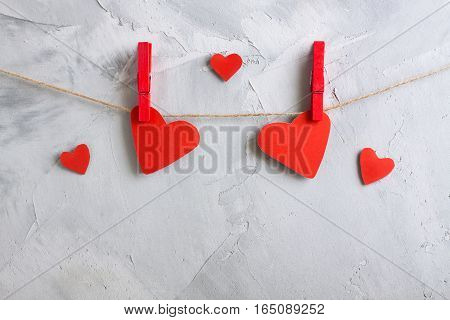 Red Paper Hearts Hanging Onto Clothespins On A Rope.