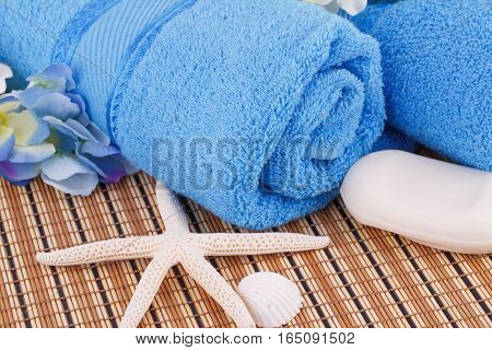 Blue towels with flowers and soap starfish closeup picture.