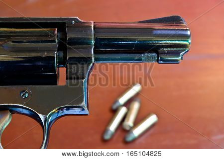 Revolver with bullets on brown wooden table