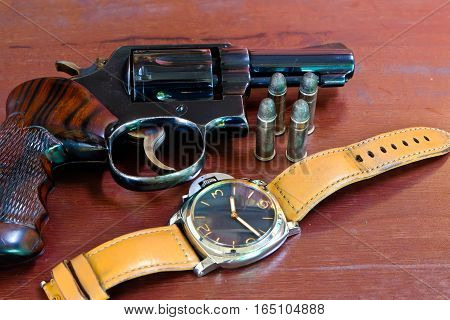 Revolver with bullets on brown wooden tables and clocks