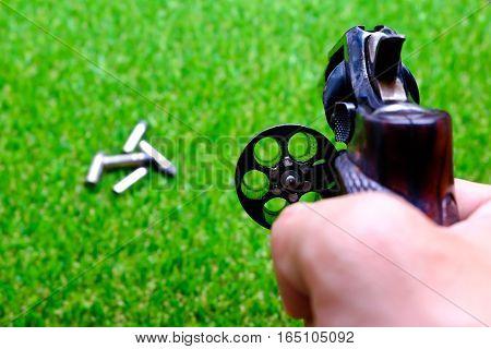 Revolver gun in hand on grass background