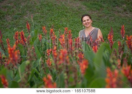 Cheerful Girl In The Flower Bed In The Park