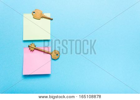 Adhesive note post and keys on a blue background