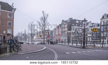 Amsterdam Netherlands- December 30 2016: Citizens have a rest on a bench. In the parapet there are bikes