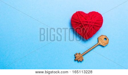 Golden Key to a red heart on a blue background. Love Valentine's Day