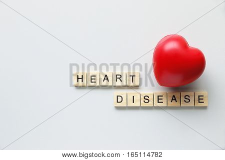 HEART DISEASE text word made with wood blocks and Red Heart on table.Concept healthcare.