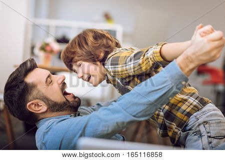 Like plane. Delighted bearded man holding his mouth open keeping hands of his son in his hands while smiling and looking at him