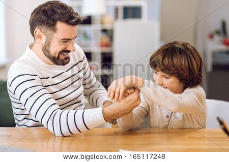 Happy time. Attractive bearded male wearing stripped sweater looking at his son while playing with him