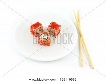 Three pieces of sushi with fish roe Masago lies on a plate with chopsticks isolated over white background closeup