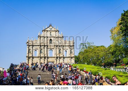 Macao China - December 9 2016: Tourists and local residents walk pass and take photos at The Ruins of St. Paul's in sunny day crowded tourist in blue sky sunny day