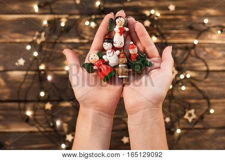 Female hands holding vintage wooden christmas toys on blurred christmas background