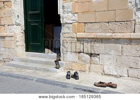 Row of shoes queuing to the entrance to the Turkish mosque on the quayside Chania Crete Greece Europe.