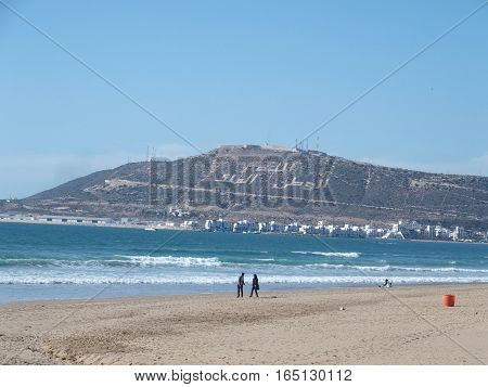 Couple on beach in travel AGADIR city in MOROCCO landscape, clear blue sky in warm sunny winter day. Three Arabic words on northwest of Mount Agadir, means God, King and Nation, AFRICA, FEBRUARY.