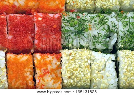 Many fresh sushi rolls with Masago roe, sesame and fenel as background closeup