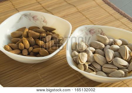 Two bowls of almonds and pistachios. Healthy meals snacks