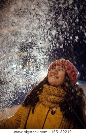 the girl's portrait in the winter who throws up snow. contrast in the light of city lamps. emotions