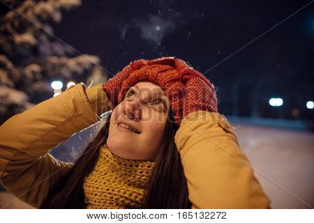 the girl's portrait in the winter against the background of the evening city which to something is surprised. in the light of city lamps.